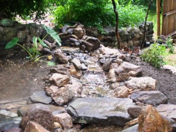 Stream through fence by natural earth garden designs for Garden stream designs
